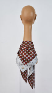 Printed grey and burgundy silk carre tied around neck