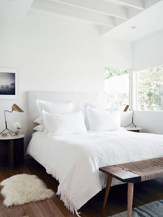 A calming bedroom with soft white linens and simple details.