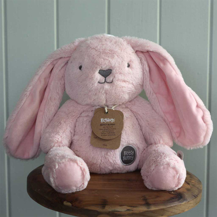 large pink bunny soft toy sitting on stool