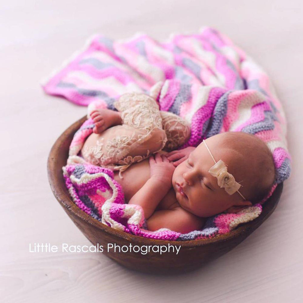 baby in basket with crochet baby blanket pink
