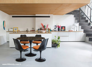 The beautiful Portoro Marble Tulip Table is perfect with black Tulip Chairs and orange cushions