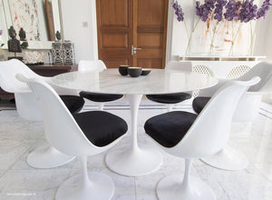 Close up view of Marble round Tulip table and chairs with black cushions