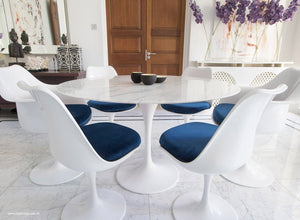 Close up view of Marble round Tulip table and chairs with blue cushions