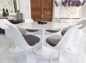 Close up view of Marble round Tulip table and chairs with grey cushions