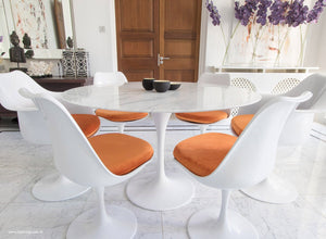 Close up view of Marble round Tulip table and chairs with orange cushions