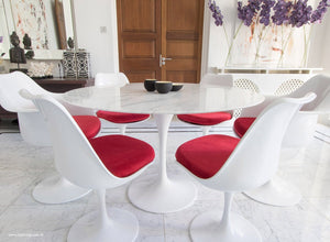 Close up view of Marble round Tulip table and chairs with red cushions