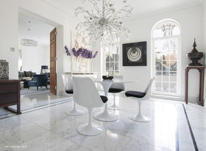 Tulip marble round dining set with grey cushions under chandelier