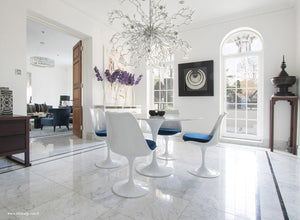 Tulip marble round dining set with blue cushions under chandelier