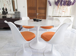 Main view of 120cm marble Tulip table, 4 tulip side chairs with orange cushions