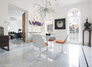 Tulip marble round dining set with orange cushions under chandelier