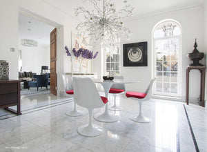 Tulip marble round dining set with red cushions under chandelier