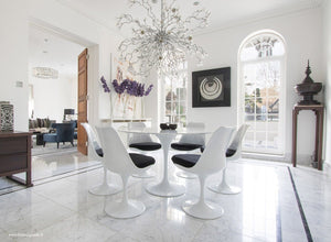 Sun room with chandelier, marble tulip table and black cushioned tulip chairs