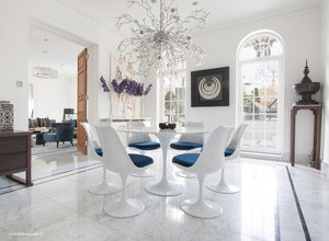 Sun room with chandelier, marble tulip table and blue cushioned tulip chairs