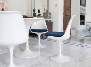 Tulip Chair with a blue cushion in dining room with marble floor