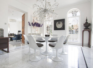 Sun room with chandelier, marble tulip table and grey cushioned tulip chairs