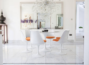 Circular marble Tulip Table and six Tulip Chairs with orange cushions