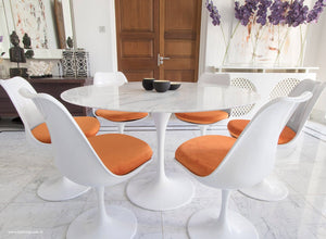 Close up of Tulip Table in marble & matching Tulip Chairs in orange