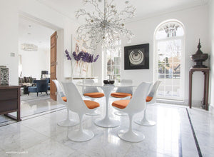 Sun room with chandelier, marble tulip table and orange cushioned tulip chairs