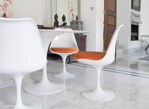 Tulip Chair with a orange cushion in dining room with marble floor