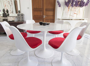 Close up of Tulip Table in marble & matching Tulip Chairs in red