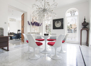 Sun room with chandelier, marble tulip table and red cushioned tulip chairs