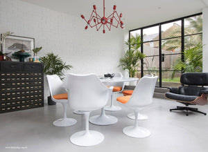 Side view of Tulip table set with 6 chairs in orange cushions