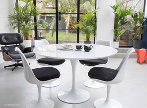 The white laminate Tulip Table with a 120cm top with 4 matching side chairs in black