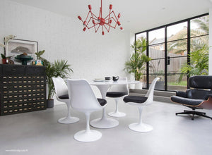 Main view of a 120 cm Tulip table in white with 4 mathcing tulip side chairs with black cushions