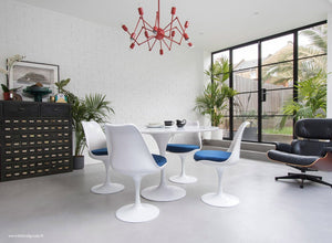 Main view of a 120 cm Tulip table in white with 4 mathcing tulip side chairs with blue cushions