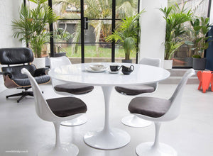 The white laminate Tulip Table with a 120cm top with 4 matching side chairs in grey