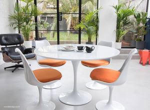 The white laminate Tulip Table with a 120cm top with 4 matching side chairs in orange