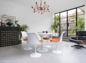 Main view of a 120 cm Tulip table in white with 4 mathcing tulip side chairs with orange cushions