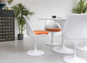 The Eero Saarinen Tulip Side Chair with a orange fitted cushion