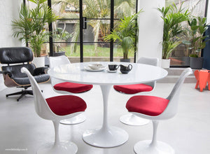 The white laminate Tulip Table with a 120cm top with 4 matching side chairs in red
