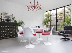 Main view of a 120 cm Tulip table in white with 4 mathcing tulip side chairs with red cushions