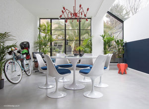 Garden room with white tulip table and chairs with blue cushions