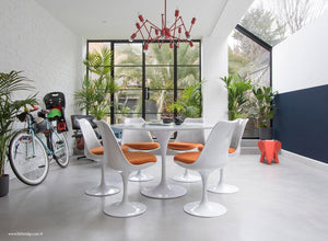 Garden room with white tulip table and chairs with orange cushions