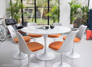 120cm White Tulip Table main view with 6 matching chairs with orange cushions