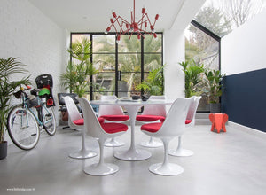 Garden room with white tulip table and chairs with red cushions