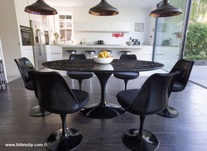 The beauty of the black Portoro marble Tulip Table is enriched by the black cushions of the matching chairs