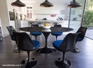 The beauty of the black Portoro marble Tulip Table is enriched by the blue cushions of the matching chairs