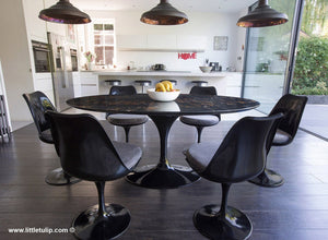 The beauty of the black Portoro marble Tulip Table is enriched by the grey cushions of the matching chairs