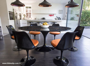The beauty of the black Portoro marble Tulip Table is enriched by the orange cushions of the matching chairs