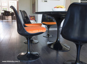 Black dining set includes 6 of the Tulip Side Chairs with fitted orange velvet like cushions