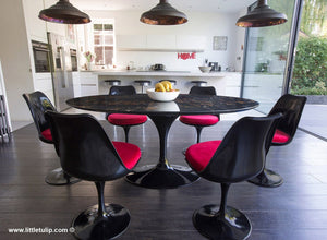The beauty of the black Portoro marble Tulip Table is enriched by the red cushions of the matching chairs