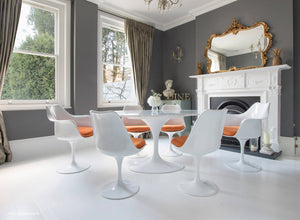 orange cushioned tulip side and arm chairs with a 170cm oval marble table