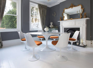 Edwardian dining room with marble Tulip Table and 6 Tulip chairs with orange cushions
