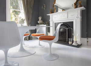 Tulip Side Chair with orange cushion in classic dining room setting