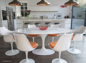 Main view of 170cm White table with four side and two tulip arm chairs with orange cushion
