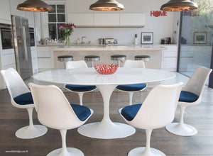 Close up of white tulip table and chairs with blue cushions in front of kitchen bar